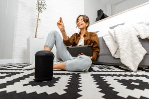 woman-with-a-smart-speaker-and-tablet-at-home